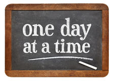 One day at a time on blackboard. One day at a time - white chalk text on a vintage slate blackboard royalty free stock photo