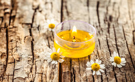 One decorative yellow candle or tea light. With some daisies on a vintage old board for wellness or relax cards and calendars royalty free stock photo