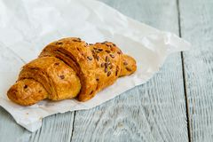One delicious croissant with golden crust and sprinkled with seeds on a white paper. One hot delicious croissant with golden crust and sprinkled with seeds on a royalty free stock photos