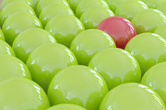 One different ball standing out from the crowd. Red ball is different and is standing out from the crowd of green balls. Concept for someone like a company Stock Photography