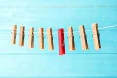 One different clothes peg among others hanging on rope. Against color background royalty free stock photos