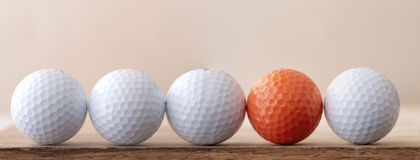 One Different Golf Ball. One orange golf ball in still life with white golf balls in horizontal banner Royalty Free Stock Image