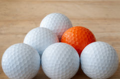 One Different Golf Ball. One orange golf ball in still life with white golf balls Royalty Free Stock Image