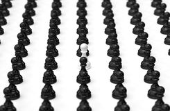 One different pawn. 3d army of black pawns with white in the middle Royalty Free Illustration