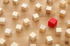 One different red cube block among wooden blocks. Individuality, leadership and uniqueness concept. Royalty Free Stock Photo