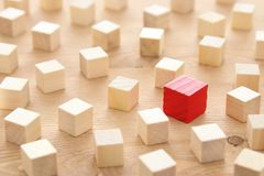 One different red cube block among wooden blocks. Individuality, leadership and uniqueness concept. One different red cube block among wooden blocks stock images