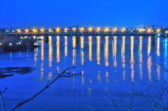 One Dim Light. This photograph shows a bridge at dusk with lights reflecting in the river below Royalty Free Stock Image