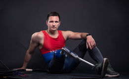 One disabled man, prosthetic leg, athlete. Sitting on floor, black background Stock Photo