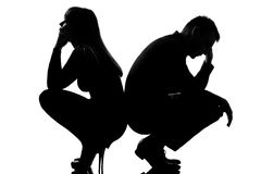 One dispute sad couple man and woman. One sad caucasian couple men and women crouching back to back in studio silhouette isolated on white background Stock Photos