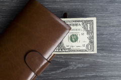 One dollar banknote in long brown wallet Stock Photography