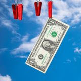One dollar banknotes on the clothes-peg. Against the blue sky. Money laundering concept royalty free stock image