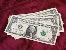 One Dollar notes, United States over red velvet background. One Dollar banknotes money (USD), currency of United States over crimson red velvet background Stock Photo