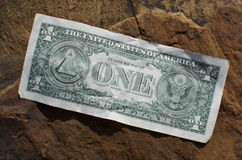 One Dollar Bill. A dollar bill lays on a rock outside Royalty Free Stock Photo