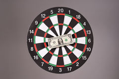 One dollar bill on a dartboard Stock Photo