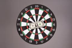 One dollar bill on a dartboard Stock Photo