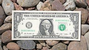 One Dollar Bill. A dollar bill lays on a stones Stock Photo