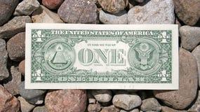 One Dollar Bill. A dollar bill lays on a stones Stock Photography