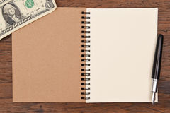 One dollar bill and pen with notebook  for background. Stock Image