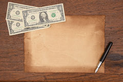 One dollar bill and pen with old papers for background. Stock Images