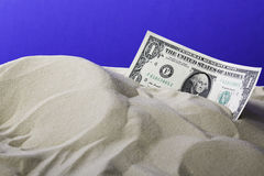 One dollar bill in sand with blue background Royalty Free Stock Images