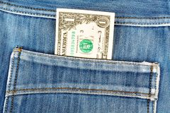 One dollar bill sticking in the back pocket of denim jeans Stock Photography