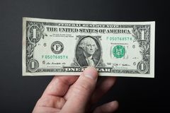 One dollar close-up in hand on a black background royalty free stock photos