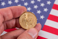 One dollar coin in hand against flag. One dollar coin in hand against usa flag Royalty Free Stock Photography