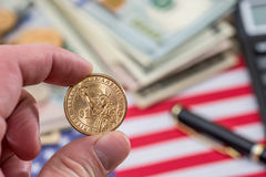 One dollar coin in hand. Against usa flag Royalty Free Stock Image