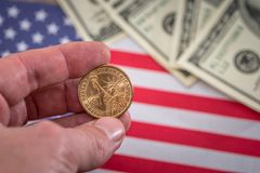 One dollar coin in hand against usa flag. One dollar coin in hand against usa flag Stock Image