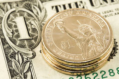 One dollar coin on note. Three new dollar coins on an old dollar note Royalty Free Stock Photo
