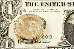 One dollar coin on note. Three new dollar coins on an old dollar note Royalty Free Stock Image
