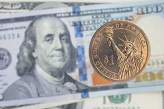 One dollar coin over dollar notes Stock Photos