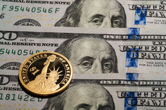 One dollar coin - The Statue of Liberty - on hundred dollars bills. Stock Image