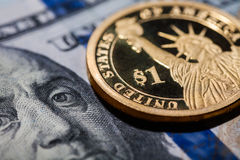 One dollar coin - The Statue of Liberty - on hundred dollars bills. Royalty Free Stock Photos