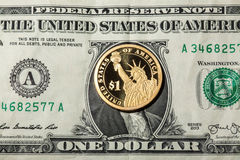 One dollar coin - The Statue of Liberty - on one dollar banknote Stock Image