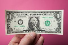 One dollar in hand on a pink background royalty free stock photography