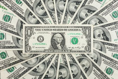 One dollar lies against the background of hundred-dollar bills Stock Photos