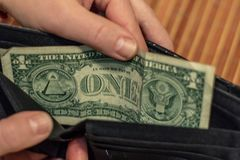 One dollar is lying in an empty leather wallet. No money in the purse. Poverty and unemployment. Old wooden rustic background royalty free stock photo