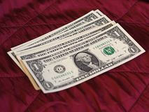 One Dollar notes, United States over red velvet background. One Dollar banknotes money (USD), currency of United States over crimson red velvet background Royalty Free Stock Images