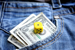 One dollar in pocket denim and a dice. One dollar banknotes in pocket denim and a dice Royalty Free Stock Photo