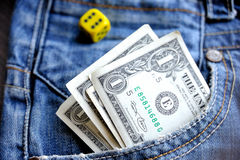 One dollar in pocket denim and a dice. One dollar in right pocket denim and a dice Royalty Free Stock Images