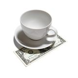 One dollar tip. Closeup of one dollar, tea cup and saucer isolated on white background royalty free stock images