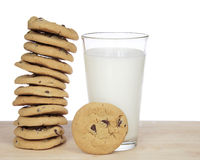 One dozen chocolate chip cookies stacked precariously. Stack of 12 chocolate chip cookies precariously stacked next to a glass of milk with one cookie standing Stock Images