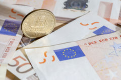 One drachma Greek coin on Euro notes Stock Photos