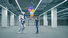 White cyborg giving balloons to a girl, side view. One droid gifts balloons to a little girl stock video footage