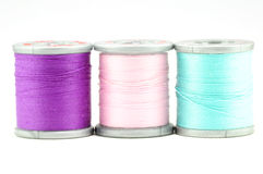 One each spool of purple, pink, and blue thread Royalty Free Stock Image