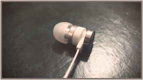 One Earphone Lying On Old Book royalty free stock images