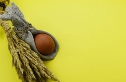 One Easter egg. Easter egg with dry plants on yellow background Stock Photo