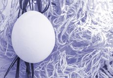 One Easter egg in a nest for Easter with blue toning effect, copy space, top view, flat lay.  royalty free stock image