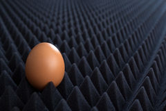 One egg on abstract bumpy black background with perspective Stock Image